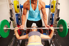 Woman bench pressing weights with assistance of trainer, front view Royalty Free Stock Image