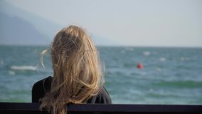 Woman On The Bench. Pretty blonde girl with long blonde hair sitting on a bench. Young woman watching people windsurfing in the sea. Handheld shot of lonely stock video
