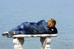 Woman on bench by sea. Rear view of woman lying on stone bench by sea Royalty Free Stock Photo