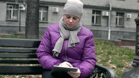 A woman on a bench with the Tablet. Video A woman on a bench with the Tablet stock video