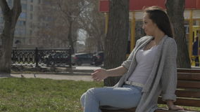 Woman on bench in windy day. Pretty young girl sitting on a bench in the park in windy spring day stock video