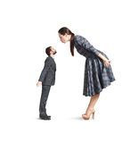 Woman bending forward and kissing small man Stock Photography