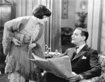 Woman bending over to talk to a man holding a newspaper. (All persons depicted are no longer living and no estate exists. Supplier grants that there will be no stock photo