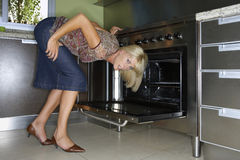 A woman bending to look at an oven. Stock Images