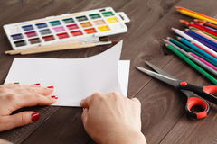 Woman bends a sheet of paper for origami Stock Photography