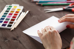 Woman bends a sheet of paper for origami Royalty Free Stock Photo
