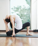 Woman bent over backwards in a yoga position in a yoga studio, side view Stock Images