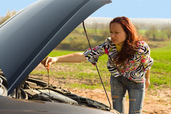 Woman bent over car engine Royalty Free Stock Image