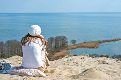Woman in a beret sits on a mountain and looking at the sea Stock Photos