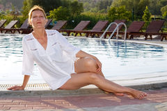 Woman besides a swimming pool Stock Photo