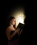 Woman with bible. A woman reading an open bible with a cross coming out Stock Images