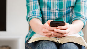 Woman with Bible and Mobile Phone Stock Photography