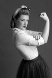 Woman biceps show-off. Woman blond biceps show-off in retro style Royalty Free Stock Photo