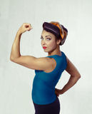 Woman biceps show-off. Woman brunette in a blue shirt with a scarf on her head and hair in a retro style biceps show-off Royalty Free Stock Photo