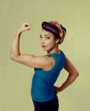 Woman biceps show-off. Woman brunette in a blue shirt with a scarf on her head and hair in a retro style biceps show-off Royalty Free Stock Photos