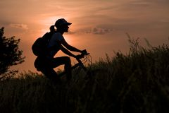 Woman on the bicycle. On sunset sky background Royalty Free Stock Photos