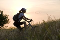 Woman on the bicycle. On sunset sky background Stock Photography