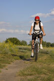 Woman on the bicycle. On flower meadow Stock Photo