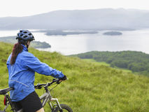 Woman With Bicycle Against Lake Stock Image