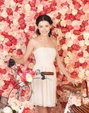 Woman with bicycle and background full of roses Royalty Free Stock Photography