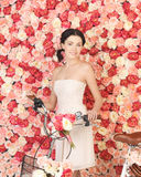 Woman with bicycle and background full of roses Stock Photography