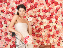 Woman with bicycle and background full of roses Stock Photos