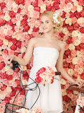 Woman with bicycle and background full of roses Stock Images