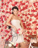 Woman with bicycle and background full of roses Stock Photo
