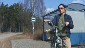 Woman with a bicycle and basket in bus stop. In summer day stock footage