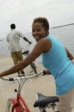 Woman With Bicycle At Beach. Portrait of a happy woman with bicycle and man in background on beach Stock Photos