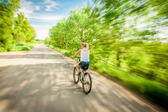 Woman on bicycle  in Blurred motion. Young woman  rushing on her bike with motion blur on country road along  green trees towards blue sky Stock Image