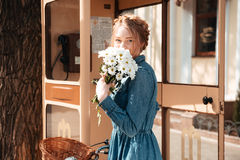 Woman with bicycle and bouquet of camomiles standing on street royalty free stock images