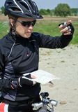 Woman on bicycle checking a map Stock Images