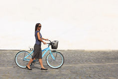 Woman with a bicycle in a city Royalty Free Stock Images