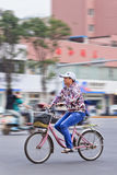 Woman on bicycle in city center, Kunming, China. KUNMING-JUNE 30, 2014. Woman on a bicycle in city center. Although fast multiplication of cars in China, the royalty free stock photography