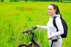 Woman with bicycle in countryside Stock Image