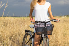 Woman with bicycle in countryside Stock Photo