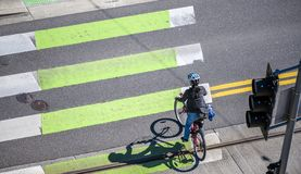 Woman on bicycle crosses the road at pedestrian crossing royalty free stock images
