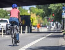 Woman in a helmet rides a bicycle on a dedicated bike path along a city street