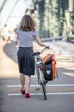Woman walks with a bicycle with fastened bag on a footpath on a bridge