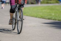 Woman with a bag rides a bicycle on a footpath
