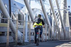 Woman in a protective vest and helmet rides a bicycle on the Tilikum Crossing bridge to the place of work