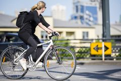 Young stylish woman cyclist in black clothes with backpack rides bicycle on the road passing through pedestrian crossing at