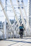 Girl rides a bicycle with two bags on each side while driving along a bike path at the Tilikum Crossing Bridge in Portland