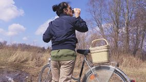 Woman with bicycle enjoy holiday near lake in spring. In summer day stock footage