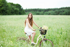 Woman on bicycle in field Stock Images