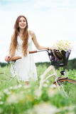 Woman on bicycle in field Stock Photo