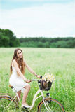 Woman on bicycle in field Royalty Free Stock Photos