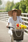 Woman with bicycle and flowers. Woman on her bike with colorful flowers Stock Photography