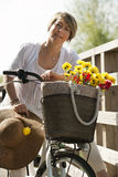Woman with bicycle and flowers. Woman on her bike with colorful flowers Stock Photos